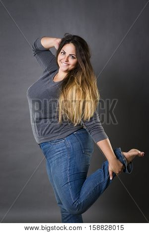 Young beautiful plus size model in blue jeans xxl woman on gray studio background