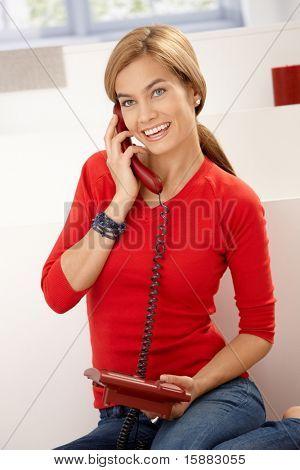 Happy Woman in roten Pullover Gespräch am Telefon sitzen auf Boden zu Hause.?