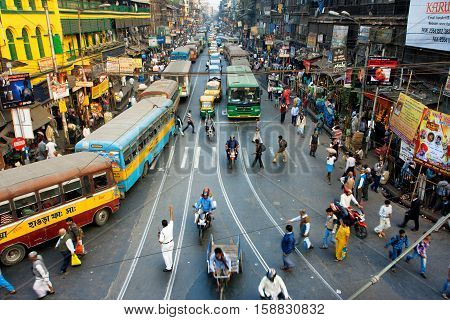 CALCUTTA, INDIA - JAN 18, 2013: Pedestrians cross the road in front of motorcycles cars and buses at the crossroads on January 18, 2013 in India. Kolkata has a density of 814.80 vehicles per km road length