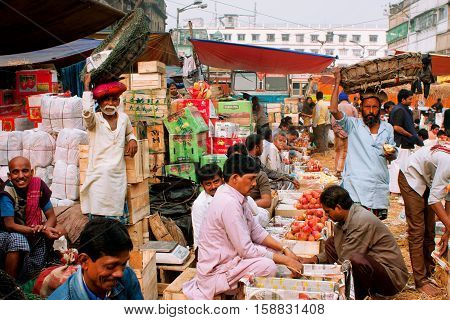 KOLKATA, INDIA - JAN 13, 2013: Fruits traders sell apples and oranges on the street market on January 13, 2013 in Calcutta. Only 0.81 perc. of Kolkata's workforce employed in primary sector agriculture.