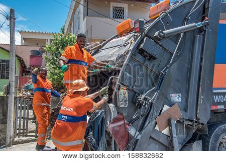 8 NOVEMBER, 2016. RIO DE JANEIRO - BRAZIL. The urban workers from the municipal COMLURB putting waste into recycling garbage truck
