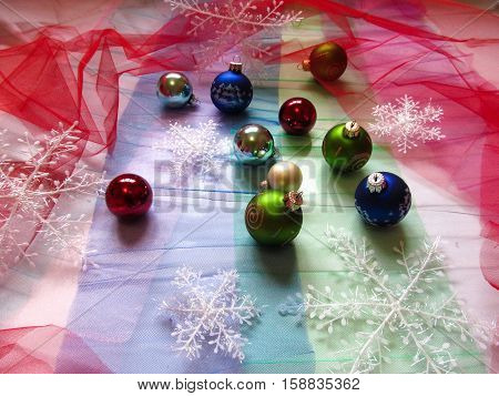 Balls and snowflakes on the Christmas tree. Holiday decorations are scattered on multicolored tulle