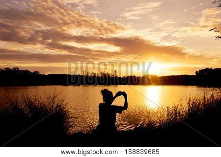Silhouette of woman taking picture at the lake