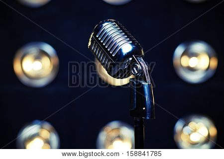 Close-up shot of retro silver microphone on spotlights blurred background. Microphone isolated on white background. Classical vintage standing microphone