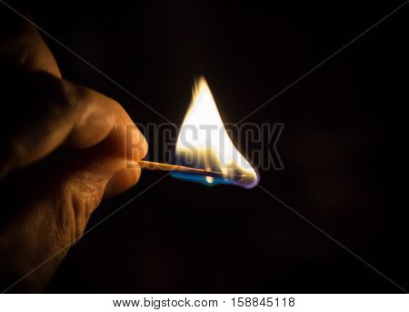 amazing beautiful closeup view of human hand holding burning matchstick in darkness