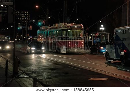 Toronto city, Ontario, Canada, Mar. 9. 2013, beautiful amazing view of night Toronto downtown street with various transportation vehicles on the road