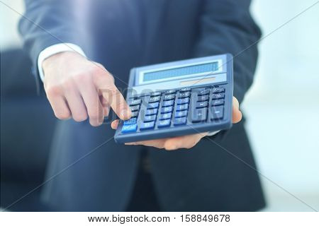 Businessman holding calculator.