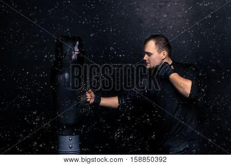 Portrait of boxer hitting the dummy in the rain. droplets bounce off the treadmill. Aquastudio shot.