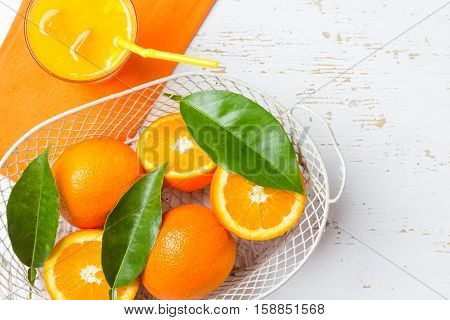 Fresh fruit orange with leaves in white basket on white background. Copy space