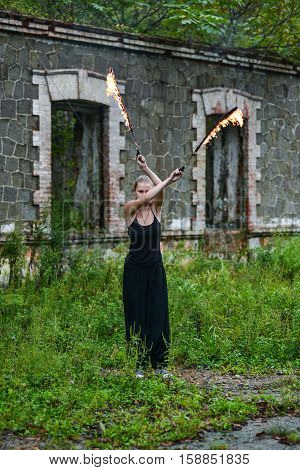 Girl in a black suit with flaming torches. fire