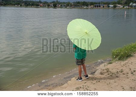 Child gazes at a lake while holding a green umbrella