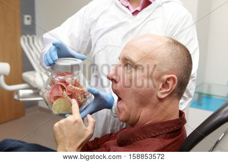 patient choosing a new set of dentures in dentist office