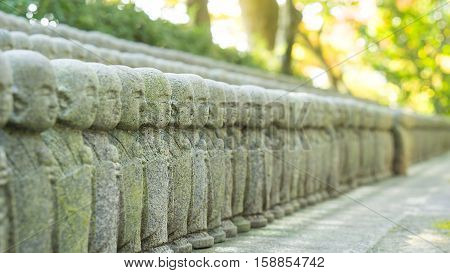 japan travel and buddha statue concept - Close up of beautiful many monk stone statue with sunlight in hasedere temple Kamamura Japan