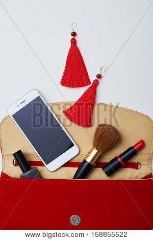 A close-up shot of bright reticule composed of brown makeup brush, big red earrings, white mobile, lipstick and nail polish. Objects placed on light territory