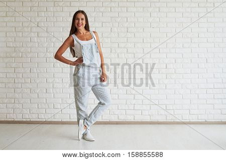 Smiling beautiful woman wear strip overalls standing with one foot on tiptoe and holding his hand on his belt, white brick wall on background