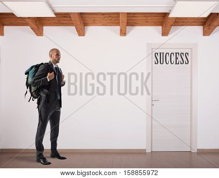 Businessman with explorer backpack forward to a door
