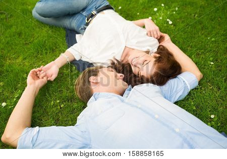 Happy couple staying together on the grass