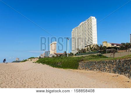 Vegetation And Empty Beach Against City Skyline