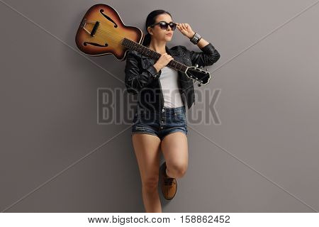 Woman in a leather jacket posing with a guitar and leaning against a gray wall