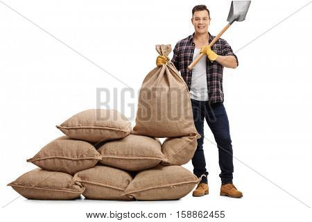 Full length portrait of a young farmer standing next to a pile of burlap sacks and holding a shovel and a sack isolated on white background