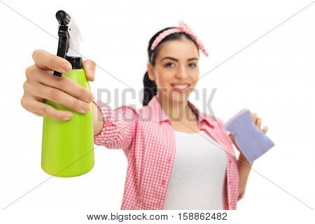 Cheerful woman cleaning with a spray and a sponge isolated on white background