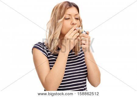 Woman lighting up a cigarette with a lighter isolated on white background