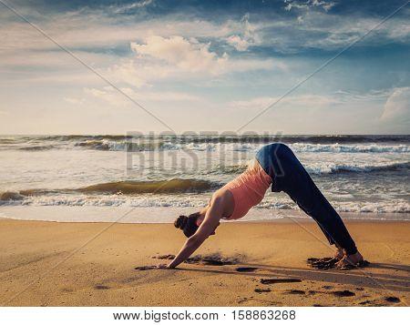 Vintage retro effect filtered hipster style image of Yoga outdoors - woman doing Ashtanga Vinyasa yoga asana Adho mukha svanasana - downward facing dog - at tropical beach on sunset. Kerala, India
