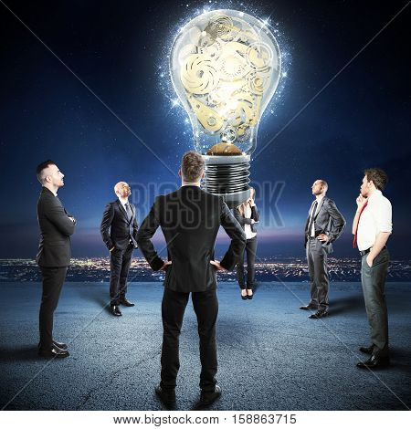 Team of businesspeople watch a big lightbulb with gears mechanism