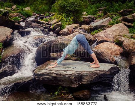 Young sporty fit woman doing yoga asana Adho mukha svanasana - downward facing dog - at tropical waterfall. Vintage retro effect filtered hipster style image.