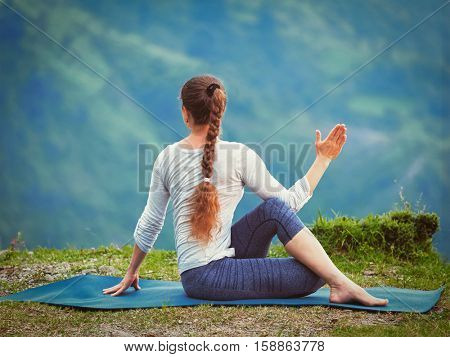 Hatha yoga outdoors - sporty fit woman doing yoga asana Parivrtta Marichyasana (or ardha matsyendrasana) - seated spinal twist outdoors in mountains. Vintage retro effect filtered hipster style image.