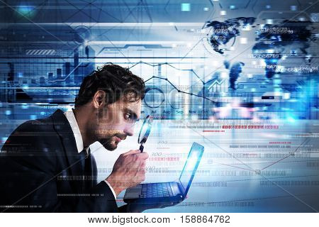 Businessman watching with magnify lens a laptop monitor