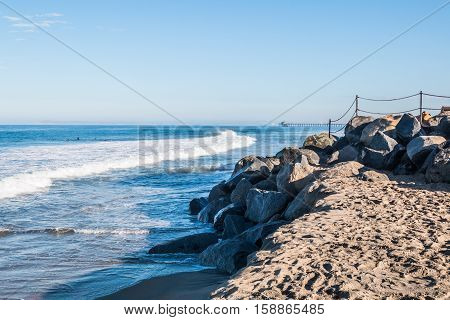 Rocky landscape with Imperial Beach fishing pier in the background.