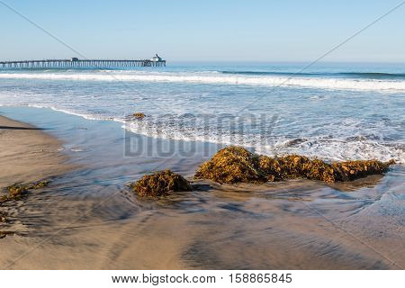 Imperial Beach fishing pier in background with waves and seaweed on beach in the foreground.