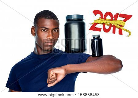 Fit man holding bottles with supplements on his biceps against digitally generated image of 3D new year with tape measure