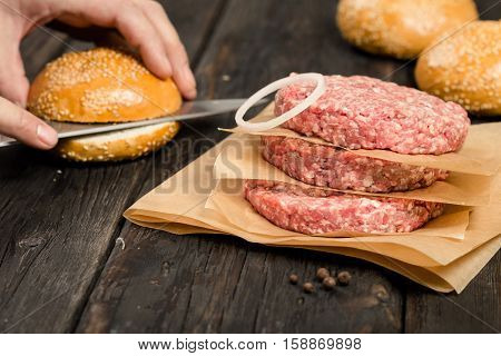 Raw ground beef meat cutlets with onion ring on wooden table close up. In the background male hand prepared burger