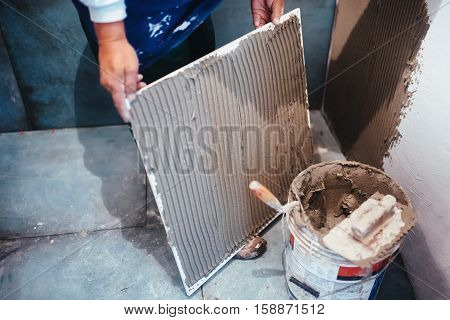 Industrial Worker Installing Bathroom Ceramic Floor Tiles, Adding Flexible Cement Adhesive With Comb