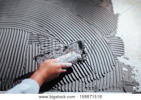 Close Up Of Worker Hand Plastering A Wall, Adding Adhesive With Comb Trowel