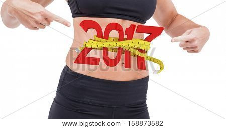 Athlete woman pointing abdominal muscle against digital image of 3D new year with tape measure