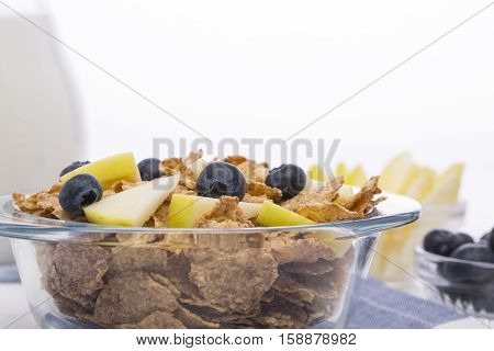 Muesli with apples and blueberries, milk carafe on a white background