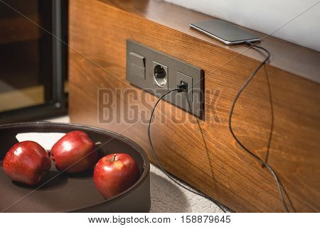 Black power socket with the switch and usb socket on the wooden rack. Above it there is a cellphone which is charging from the usb socket. In front of the rack there is a basket with three red apples.