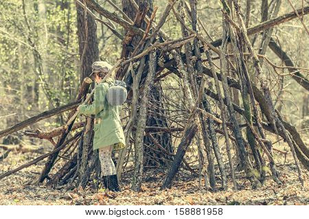 little girl in the wood near the hut with a stick in her hand. Photo in retro style