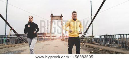 Beautiful couple jogging in sportswear on the bridge. Living healthy