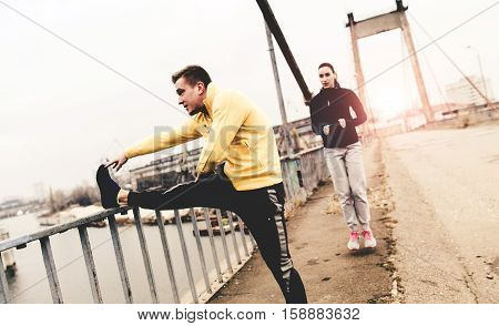 Couple young athletes in sports clothing are training on a city bridge on the sunset