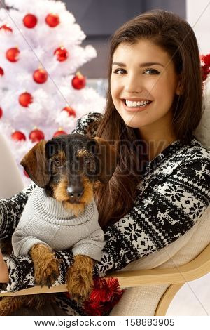 Attractive young woman holding dog on lap, smiling front of christmas tree.