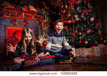 Two cheerful children playing with a toy railway near the Christmas tree and fireplace. Christmas night. Christmas decoration.