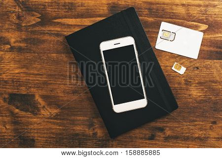 Switching SIM cards in smartphone top view of mobile phone device on desktop