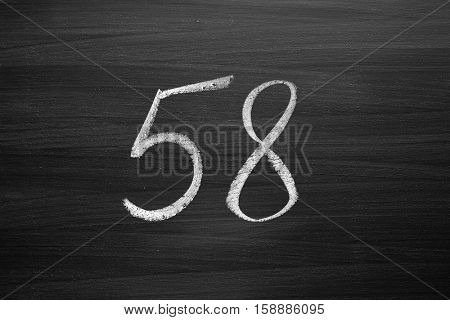 number fifty eight enumeration written with a chalk on the blackboard