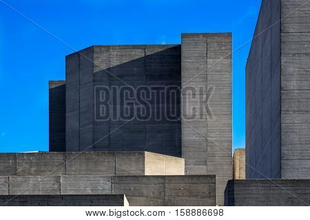 Parts of the brutalist architecture facade of the National Theatre in London against a blue sky