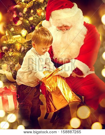 Santa Claus giving Christmas gift to child. Santa and Happy Kid. Cute little Boy and Santa Claus holding Giftbox. Christmas Holiday Scene over Decorated Christmas Tree