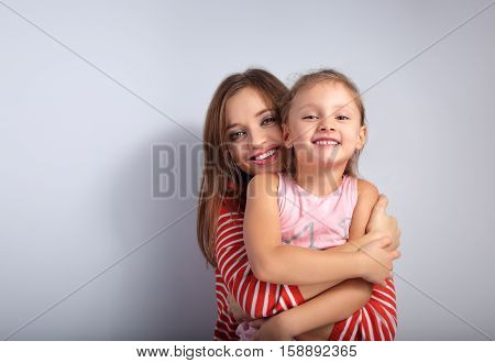 Playful Happy Mother Hugging Her Joking Grimacing Kid On Blue Background With Love